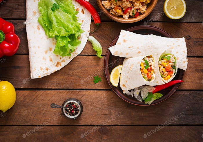 Burritos wraps with chicken meat, corn, tomatoes and peppers on wooden background. Top view