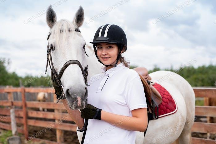 Junge lächelnde Frau im Pferdeoutfit stehen in der Nähe von weißen Rennpferd