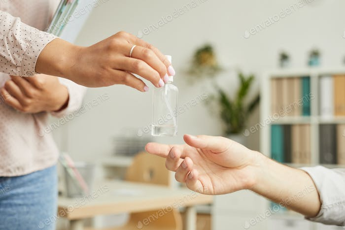 Colleagues Sharing Hand Sanitizer