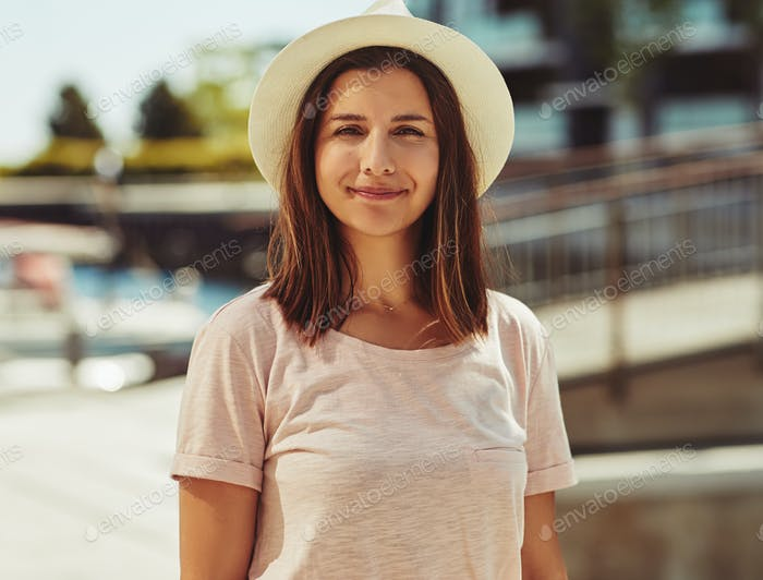 Smiling young woman standing outside on a sunny day