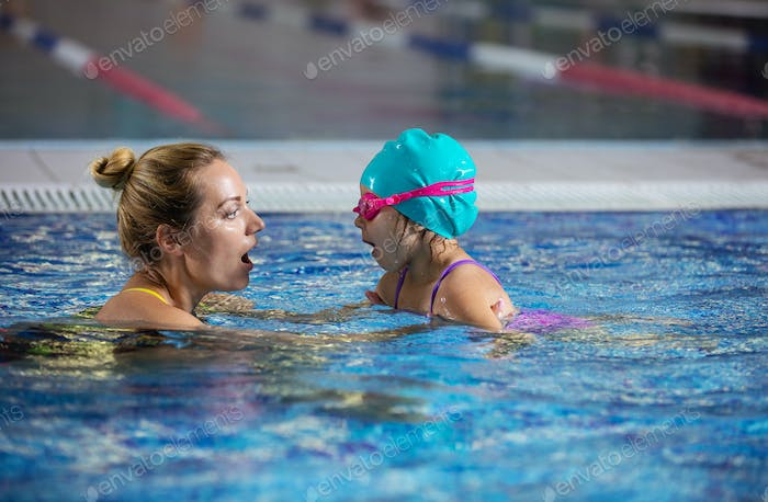 Mother or instructor teaching little girl to hold breath before
