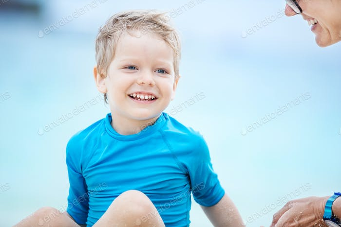 Cute little boy talking to mom on the beach and smiling