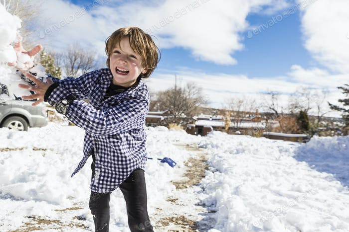 Ein sechsjähriger Junge wirft einen Schneeball