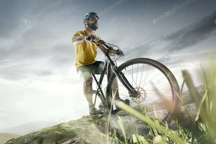 The young fit men in helmet conquering mountains on a bicycle.