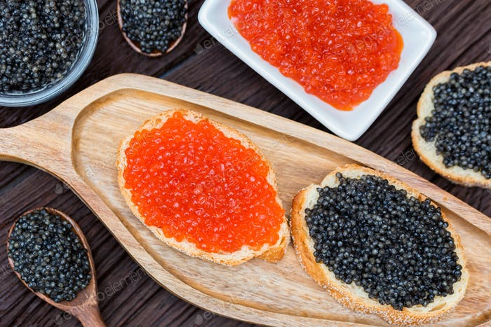 Sandwiches with black sturgeon and red salmon caviar close up