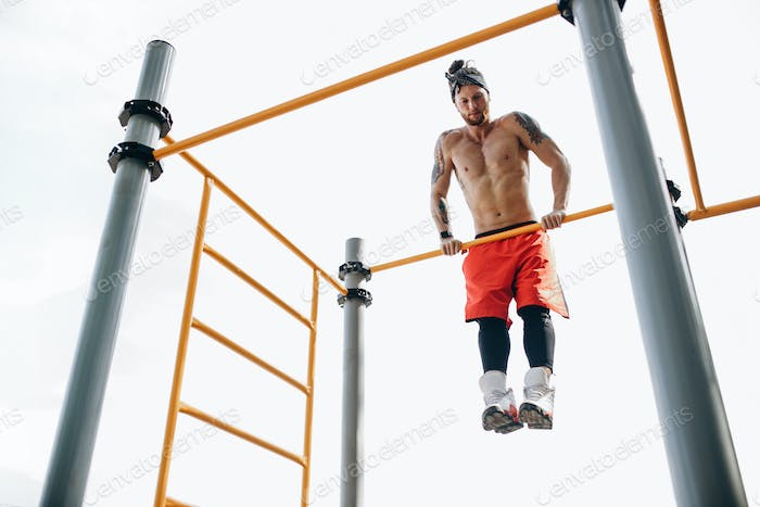 Young muscular shirtless male in stylish sport clothing doing pull ups exercises on horizontal bar