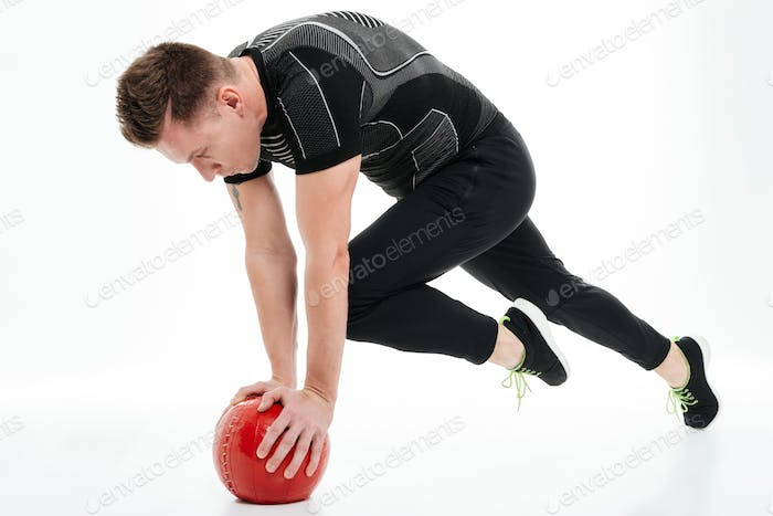 Full length portrait of a healthy athlete man doing exercises