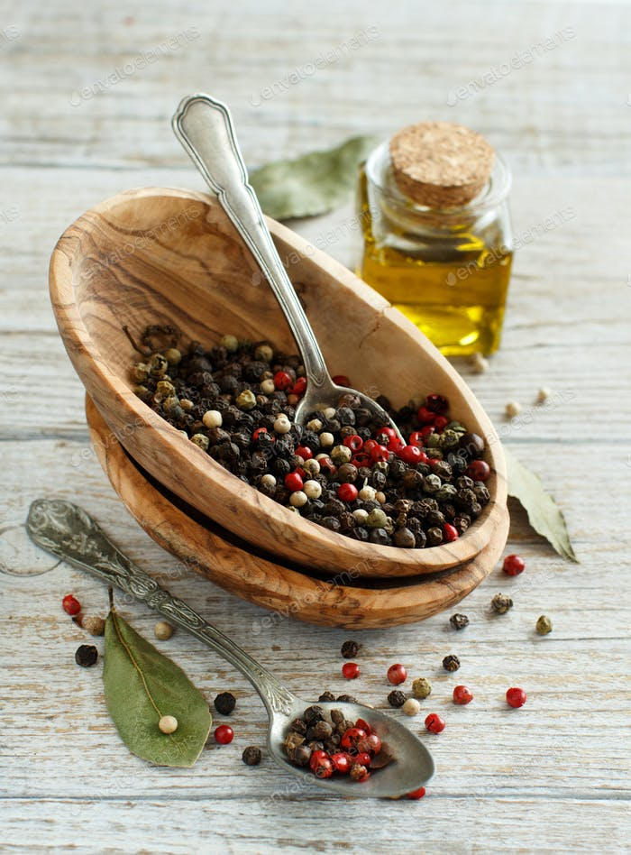 Peppercorn mix in a bowl, bay leaves  and olive oil