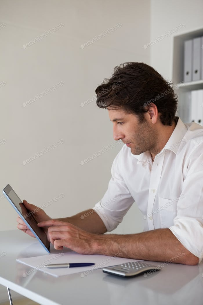 Casual focused businessman using tablet and calculator in his office