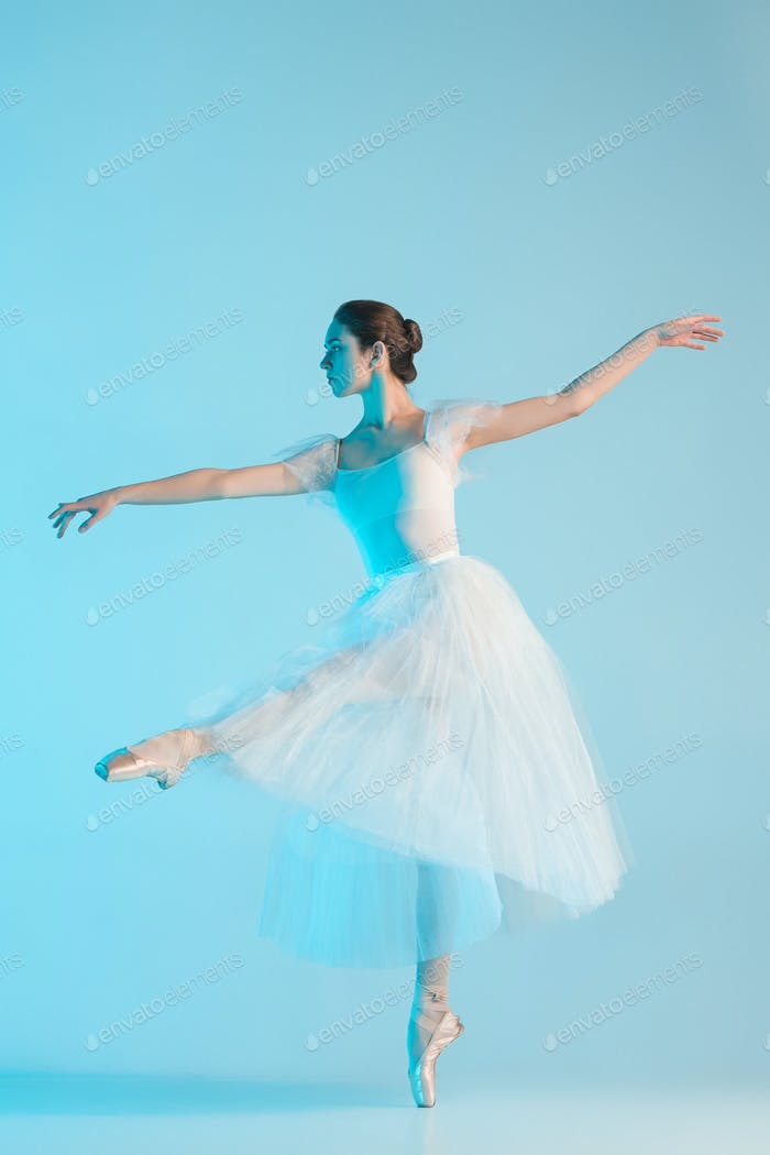 Young and incredibly beautiful ballerina is dancing in a blue studio