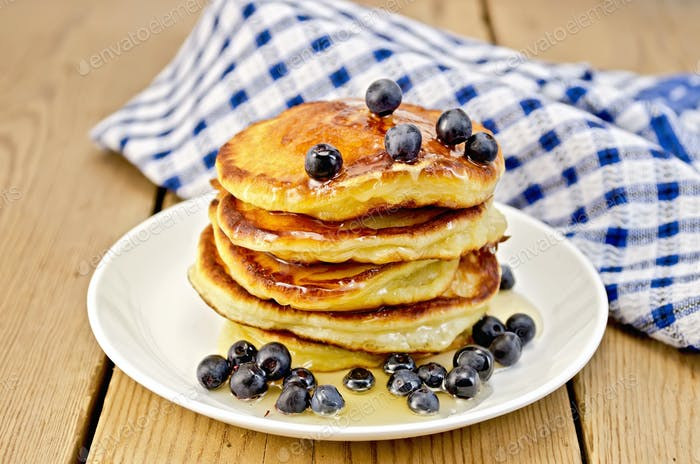 Flapjacks with blueberries and a napkin on the board