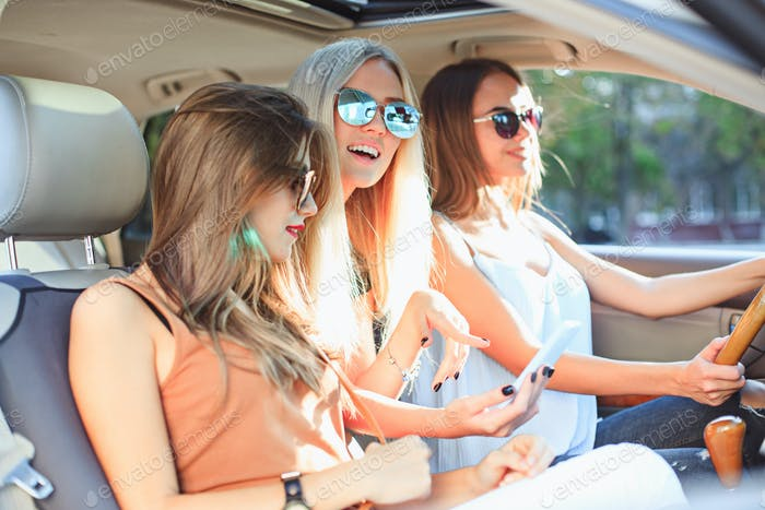The pretty european girls 25-30 years old in the car make photo on mobile phone