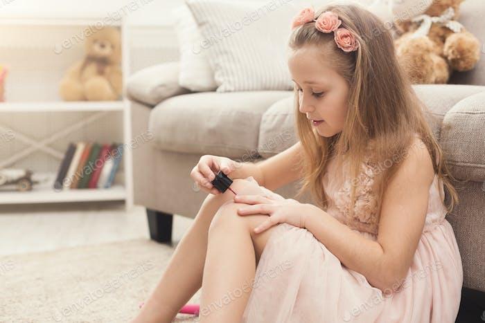Cute little girl polishing nails, sitting on floor