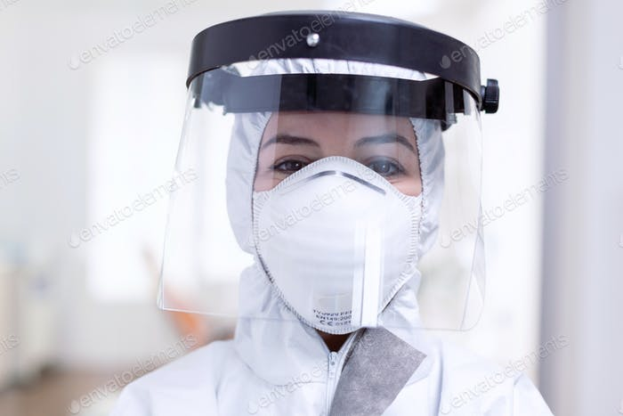 Close up portrait of exhausted doctor with face shield and face mask