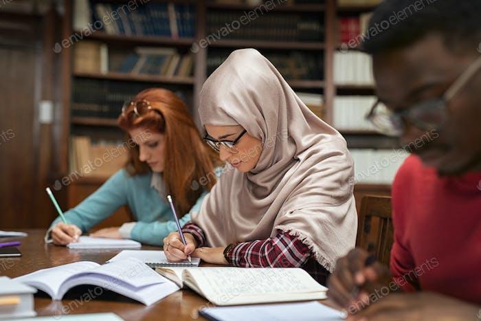Muslimische junge Frau studieren mit Klassenkameraden