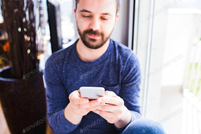 Hipster businessman working from home, holding smartphone, texti