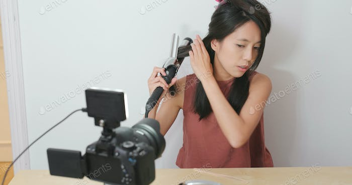 Woman making hair in front of the digital camera to take vlog on social media