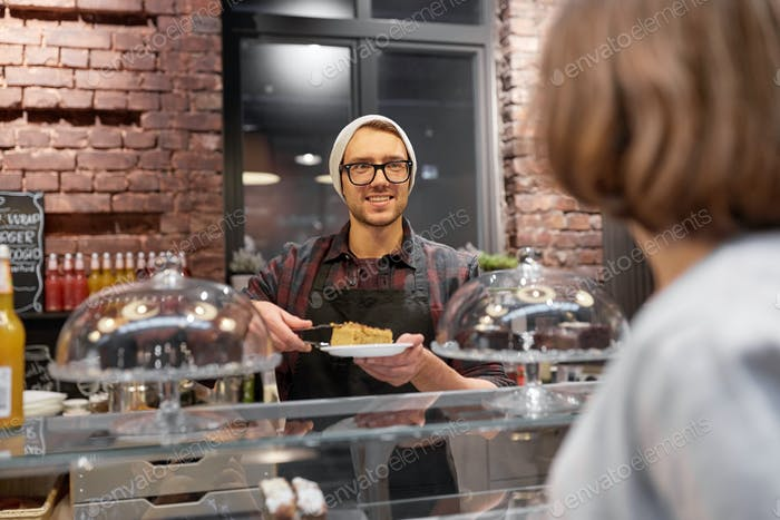 man or barman with cake serving customer at cafe
