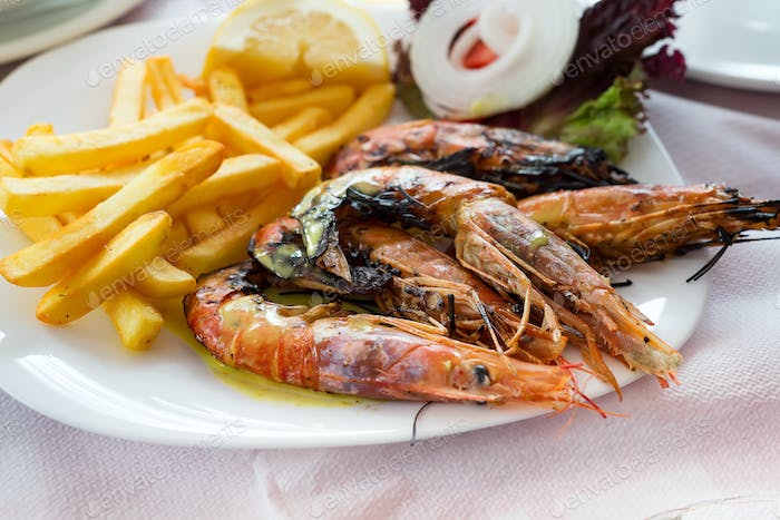 Close up big size grill shrimps with fried potato, vegetables and lemon, lunch time in restaurant