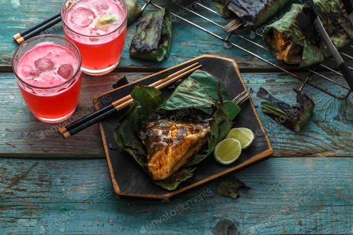 Grilled stingray wing or sambal stingray in leaf with lime and spicy dressing, malaysian cuisine