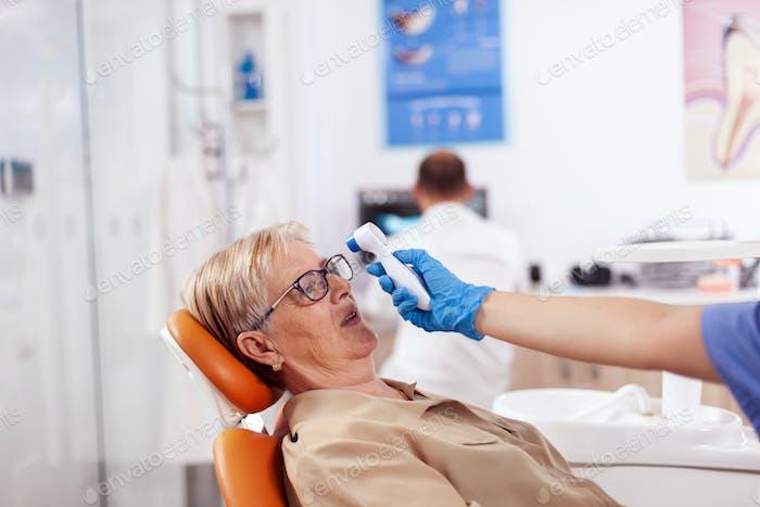 Dentist assistant holding digital body temperature indicator