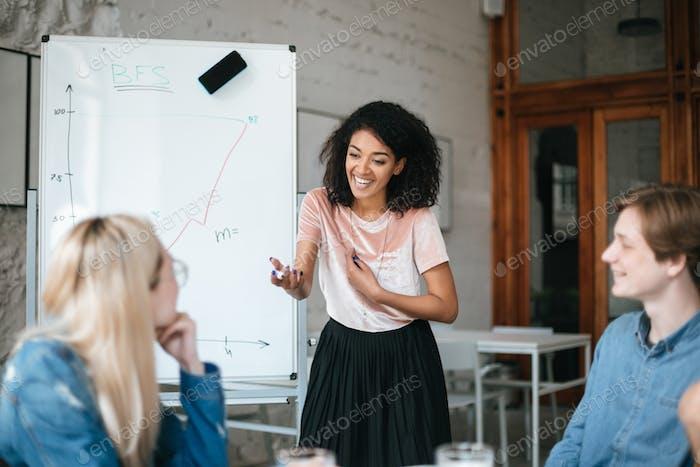 Счастливая афро-американская девушка, стоящая возле доски и обсуждающая новый проект с коллегами в офисе