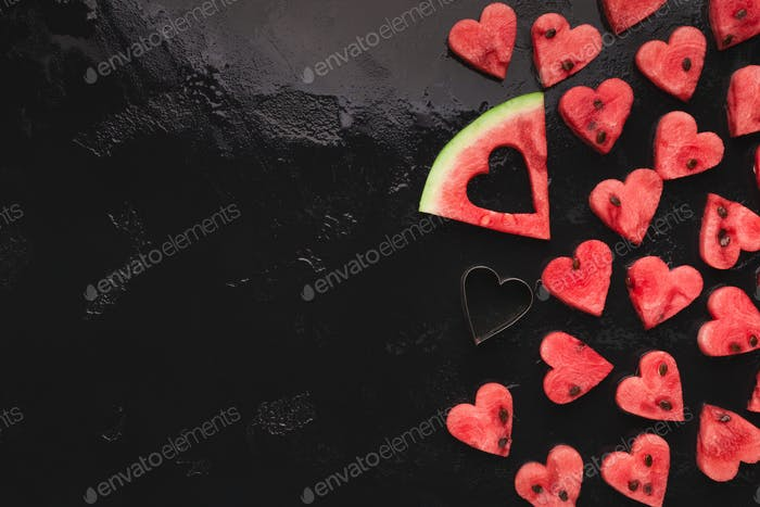 Heart shaped watermelon pieces, big slice and cutter on black