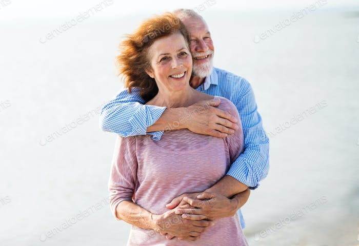 Senior couple on a holiday on a walk by the lake, hugging
