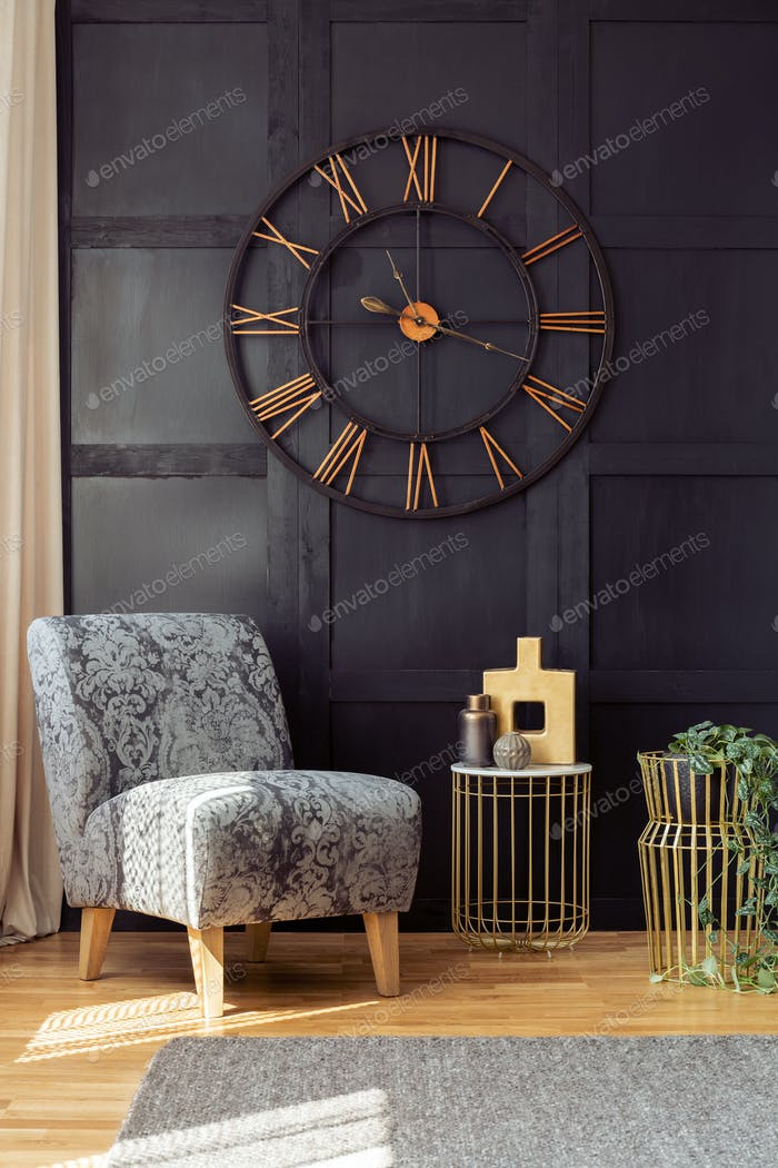 Oversized wall clock, armchair and golden table with a vase in a