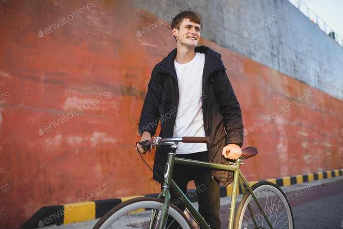Portrait of young man with brown hair walking with classic bicycle while joyfully looking aside