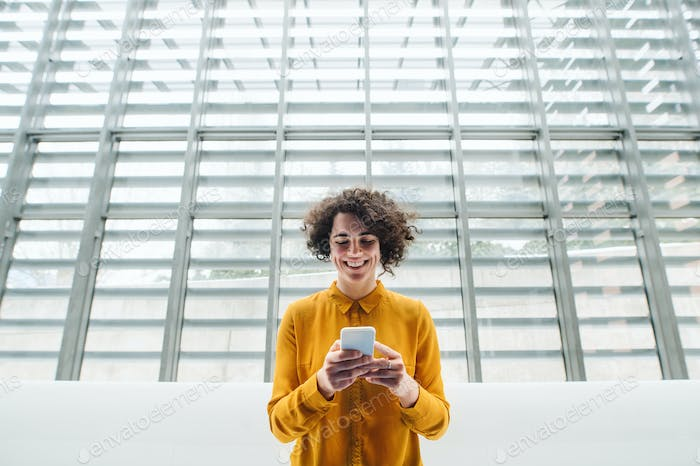 Young student or businesswoman with smartphone in a library or office