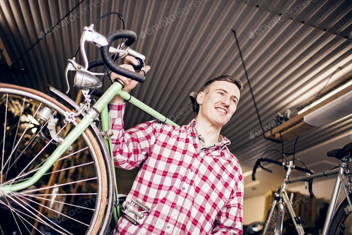 Low angle view of happy mechanic carrying bicycle in shop