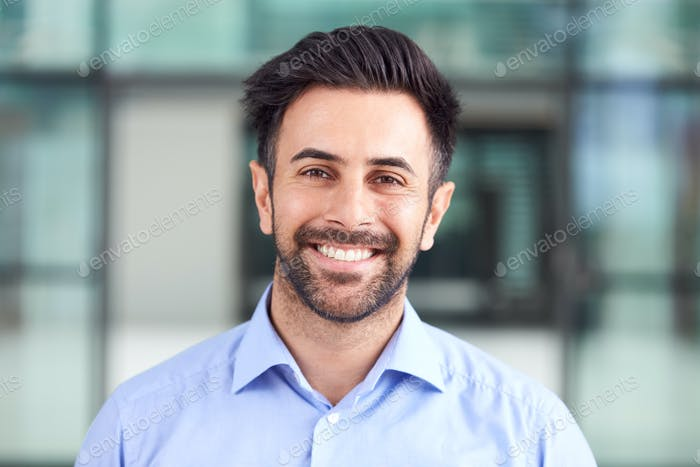 Portrait Of Smiling Businessman Standing In Lobby Of Busy Modern Office