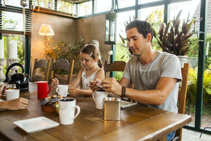 Family of three having breakfast at home