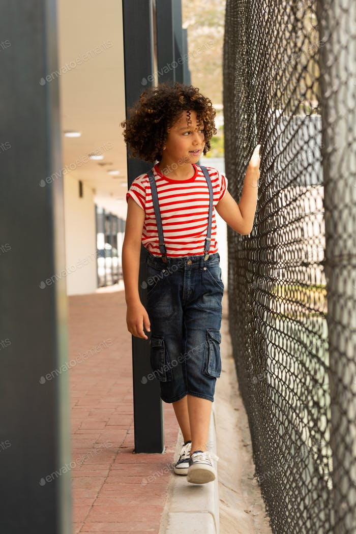 Front view of mixed-race innocent schoolgirl walking near wire mesh fence at school
