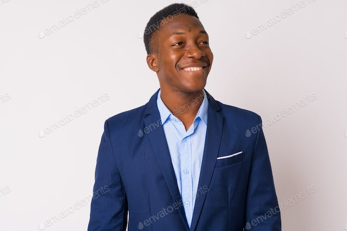 Face of young happy African businessman in suit thinking