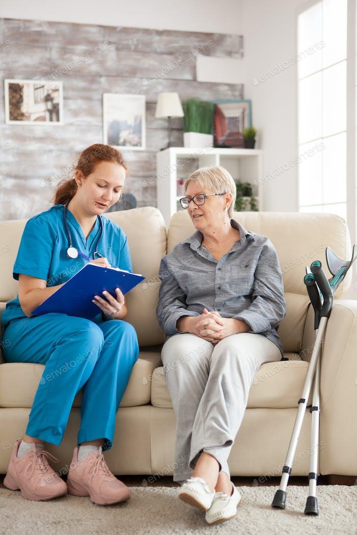 Ärztin mit Seniorin sitzend auf Couch