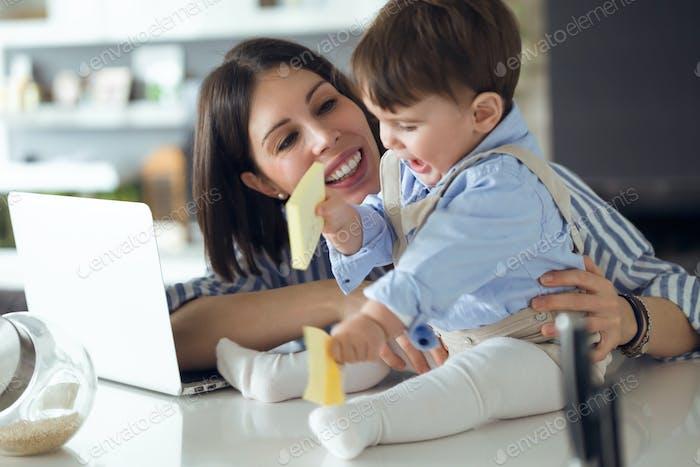 Hübsche junge Mutter mit ihrem Baby spielt mit Notebook zu Hause.