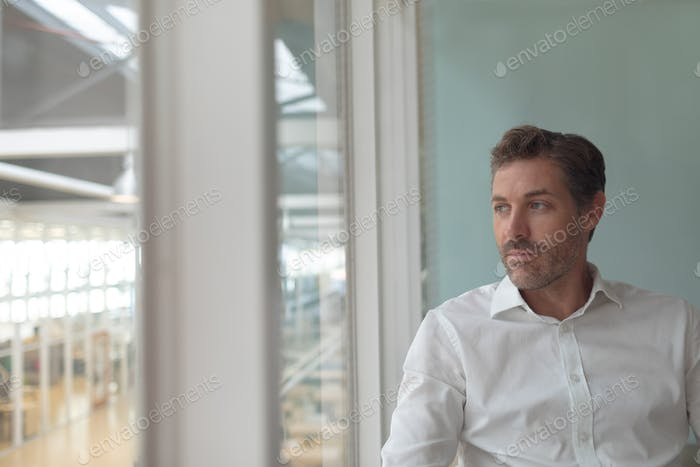 Front view of thoughtful Caucasian business male executive looking through window in a modern office