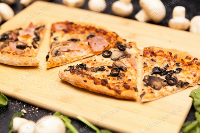 Four sliced of pizza on wooden board