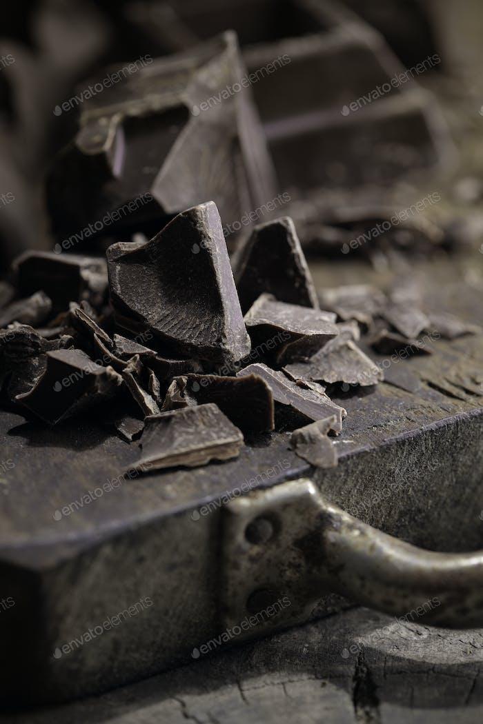 Stücke von dunkler Schokolade auf einem hölzernen Hintergrund