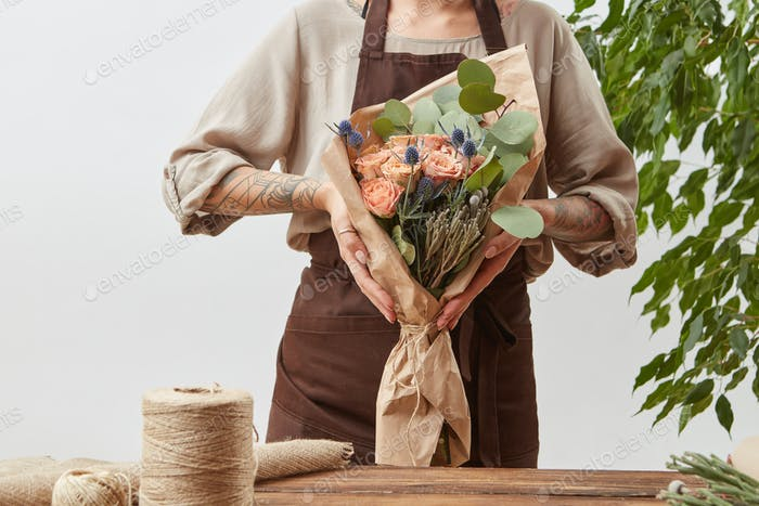 Girl's florist hands hold fresh natural bouquet from fragrant flowers living coral color roses
