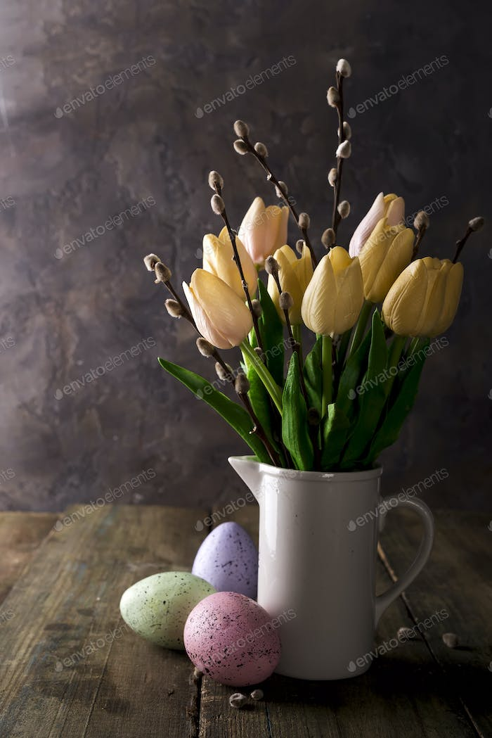 tulip flowers bouquet in pitcher and easter eggs in front of wooden wall