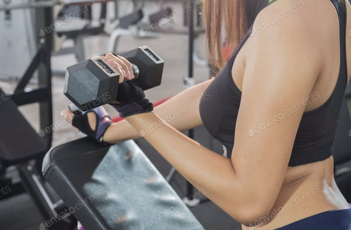 Fitness woman lifting dumbbell in hand.Focus on belly and dumbbe