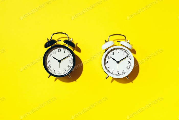 Black alarm clock and white one with hard shadow on yellow background. Top view