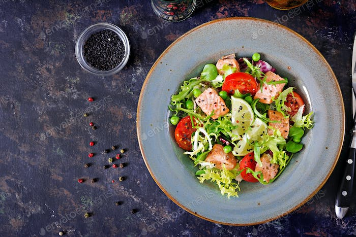 Healthy salad with fish. Baked salmon, tomatoes, lime and lettuce.