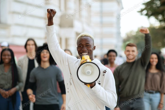 Emotional black guy activist with megaphone on the street