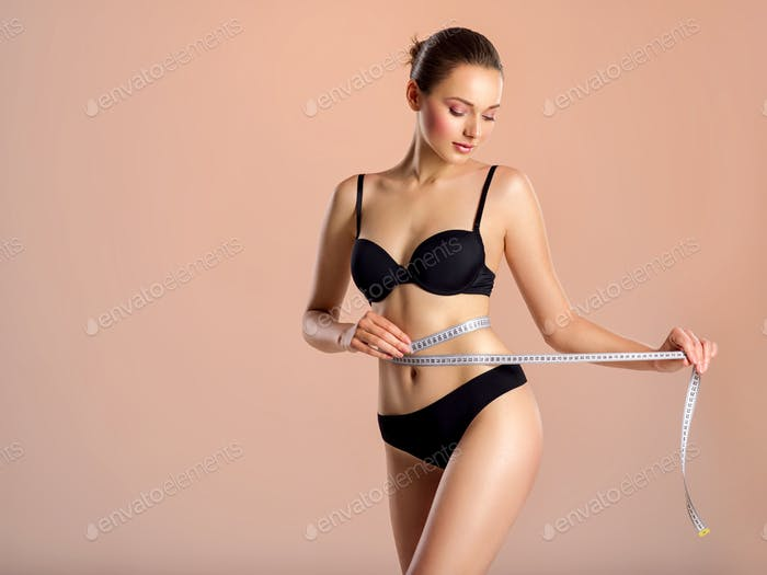 Young woman with tape and a beautiful, healthy body. Sexy woman measuring her perfect body.