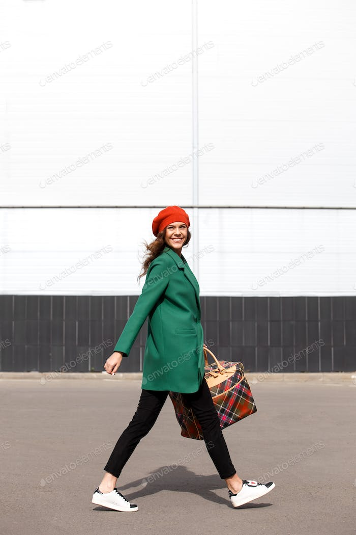 Charming stylish brunette girl dressed in a green coat and orange beret holding big checkered bag
