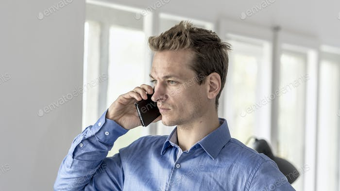 Businessman in office having a conversation on a mobile phone